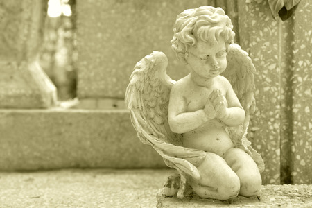 praying angel: Monument on a grave with a little angel praying