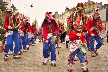 group of masked dancers with drums , performing a traditional dance Romanian