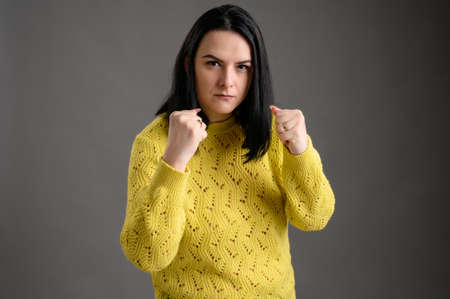 Young woman with black hair dressed casually in a yellow sweater shows her fists and get angry posing an isolated grey background Banco de Imagens