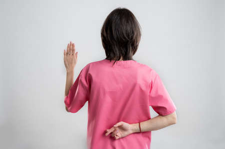 Young woman medical professional nurse or doctor dressed with pink hospital clothes, with brown hair, showing fake oath from behind posing on a white isolated backround.