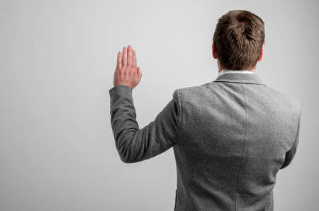 Back view of business man wearing business clothes taking oath isolated on grey background with copy space advertising area