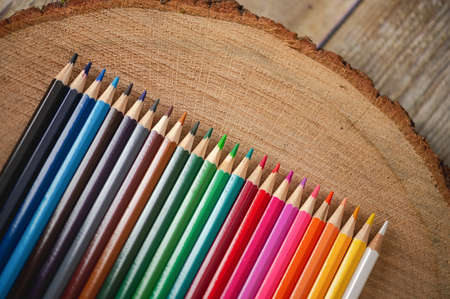 Close-up view of  rainbow colored pencils on natural wood background