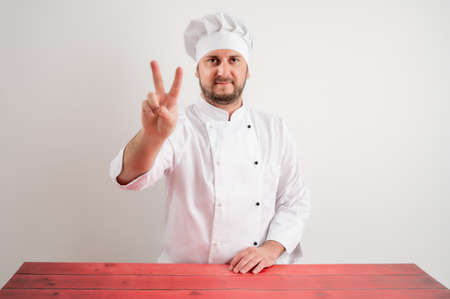 Young male chef in white uniform showing victory sign posing on a white isolated background