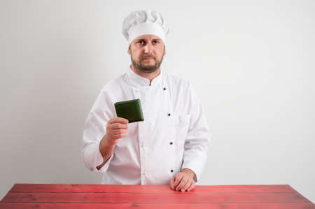 Portrait of young male chef in white uniform showing his wallet posing on a white isolated background