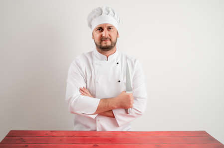 Young male chef in white uniform looking confident with the knife in his hand posing on a white isolated background