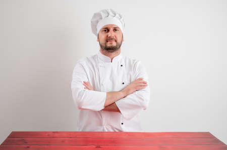 Young male chef in white uniform looking confident posing on a white isolated background