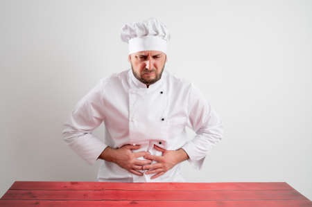 Young male chef in white uniform has stomach pain posing on a white isolated background