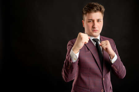 Law student with blond hair dressed in burgundy jacket, white shirt and black tie showing fists, boxing posing on isolated black background with copy space advertising area Archivio Fotografico