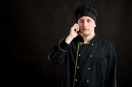 Portrait of young male dressed in a black chef suit talking on cellphone, smartphone posing on a black isolated background with copy space advertising area Stock fotó