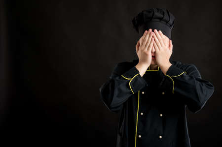 Portrait of young male dressed in a black chef suit covering eye like blind concept posing on a black isolated background with copy space advertising area