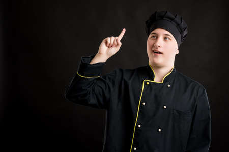 Portrait of young male dressed in a black chef suit with her finger up has come up with an idea posing on a black isolated background with copy space advertising area