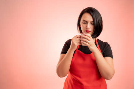 Woman employed at supermarket with red apron and black t-shirt, blow into the coffee cup isolated on red background