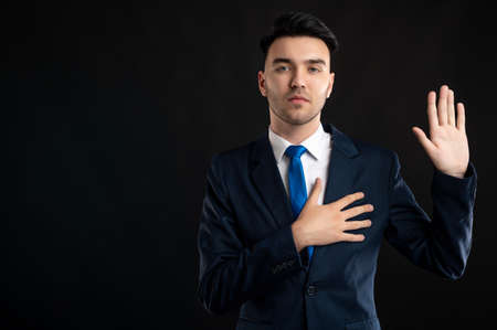 Portrait of business man wearing blue business suit and tie taking oath gesture isolated on black background with copy space advertising area