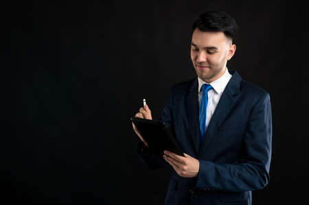 Portrait of business man wearing blue business suit and tie take notes on the tablet isolated on black background with copy space advertising area