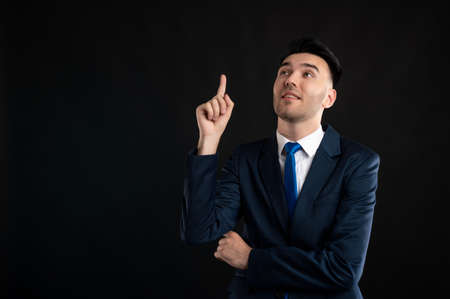 Portrait of business man wearing blue business suit and tie he thinks of an idea isolated on black background with copy space advertising area
