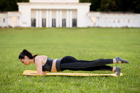 Beautiful young woman lying on a yellow mattress, pose while wearing a tight sports outfit in the park doing pilates or yoga, leg pull prone exercises