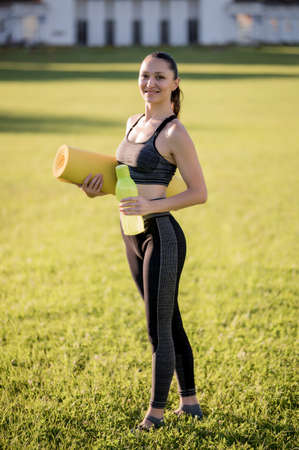 Beautiful young woman while wearing a tight sports outfit holding a yellow mattress and a bottle of water in hand, poses in the park before doing pilates or yoga exercises