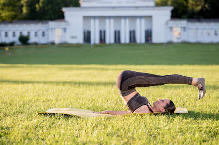 Beautiful young woman lying on a yellow mattress, pose while wearing a tight sports outfit in the park doing pilates or yoga, rolling back intermediate exercises