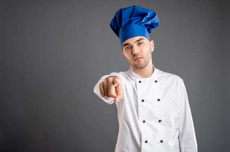 Young male dressed in a white chef suit pointing his finger posing on a gray background with copy space advertising area