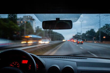 Road view from inside car natural light street and other cars is motion blurred during rain at dusk