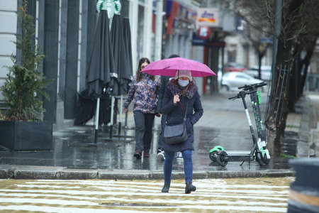 Sofia, Bulgaria - Apr 4 2021: A woman with an umbrella and protective mask crossing the street Editorial