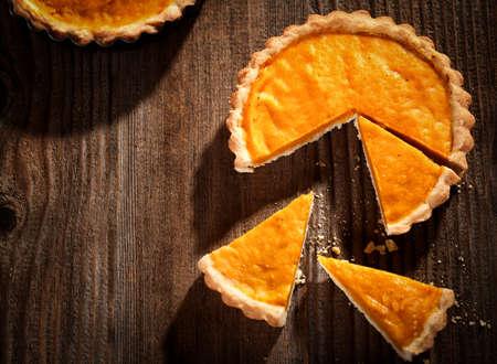 木製の背景の上にかぼちゃパイ