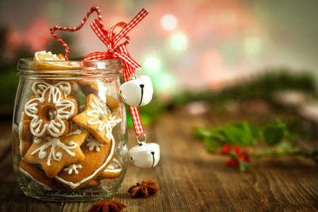 クリスマス ヒイラギと木製の背景に瓶の中のクリスマスのクッキー 写真素材