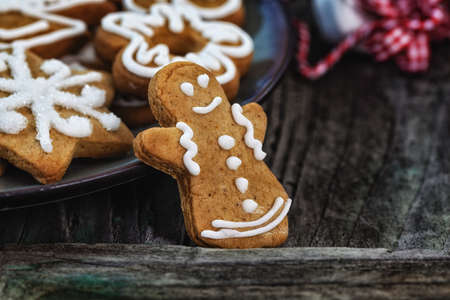 gingerbread man: Gingerbread man standing next to plate full of cookies