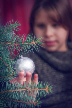decorating christmas tree: Close up of young girl decorating Christmas tree - background blur Stock Photo