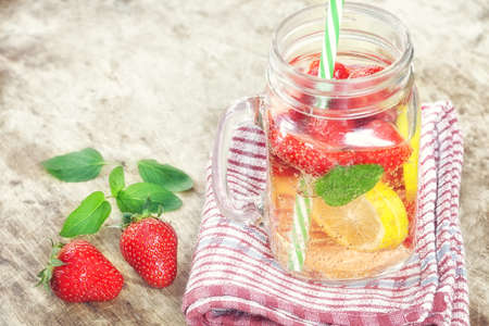 Detox Infused water with lemon, strawberry and mint on wooden background