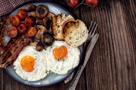 english breakfast: English breakfast with eggs, tomatoes, mushrooms, bacon, beans Stock Photo