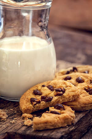 choco chips: Chocolate chip cookies with milk in bottles on wooden background