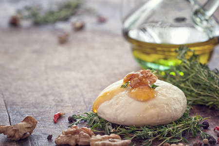 queso de cabra: Queso de cabra con miel, tomillo y frutos secos Foto de archivo