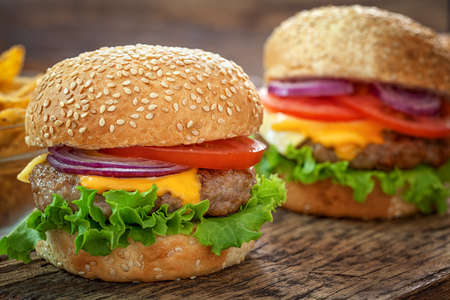 cheeseburgers: Cheeseburgers on wooden background with copy space