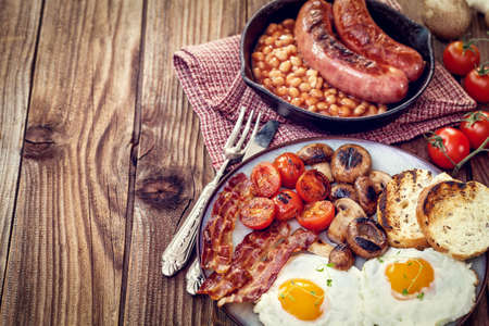 english breakfast: English breakfast with eggs, tomatoes, mushrooms, bacon and beans
