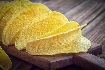 tortilla de maiz: - Tacos de tortilla de maíz amarillo mexicana, cáscara vacía a bordo de corte de madera