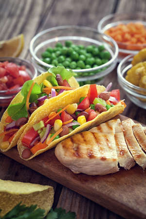 tortilla de maiz: Mexican corn tortilla tacos with vegetables and grilled chicken on wooden background