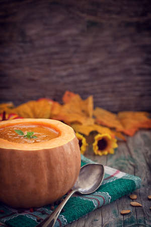 butternut: Thanksgiving Pumpkin soup on rustic background with copy space