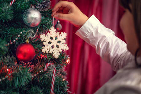 tree decorations: Young girl decorating Christmas tree Stock Photo
