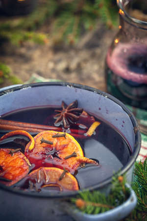 Mulled wine with spices and ingredients on wooden background