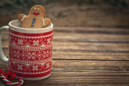 コピー スペースを持つ木製の背景にマグカップにクリスマスのジンジャーブレッドのクッキー