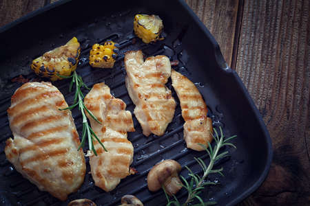 Grilled chicken breast with mushroom and rosemary on a wooden board or grill pan