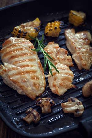 キノコと木製の板やグリル鍋にローズマリーのチキン胸肉のグリル 写真素材