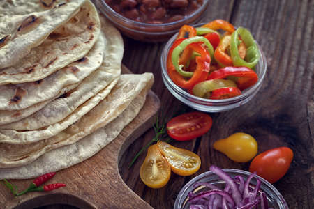 Mexican corn tortilla tacos with vegetables on wooden background Reklamní fotografie