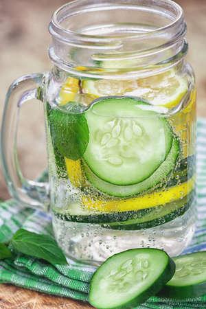 キュウリとレモンの木製の背景ホットフューズ水をデトックスします。