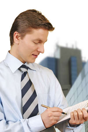 Business man holding a clipboard with corporate buildings on the background photo