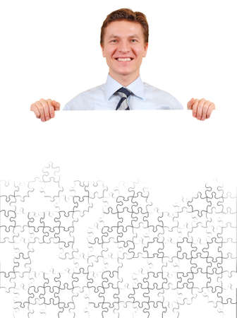 Smiling business man holding a white unfinished puzzle board  , add your text or image photo