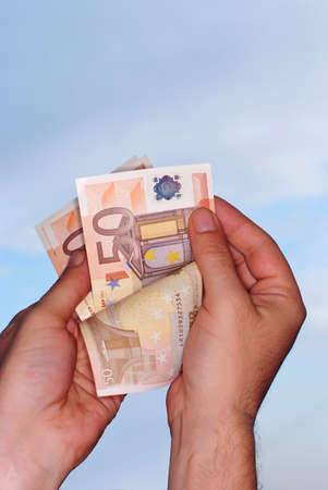 Hands holding euro against blue sky,clipping path included photo