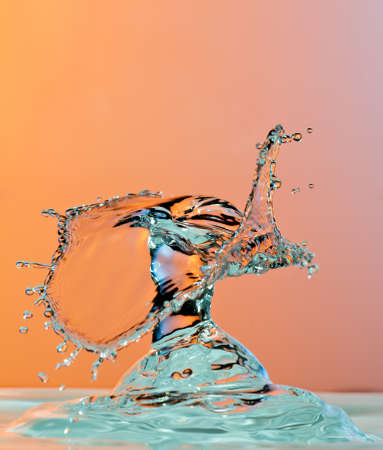 Dancing water droplet High Speed Photography on an orange background Standard-Bild