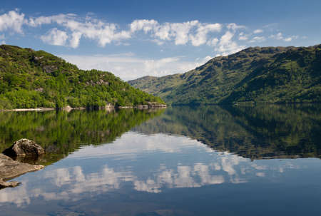 Reflections of treed and clouds on Loch Lomond, Scotland, United Kingdom photo